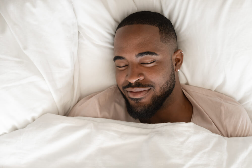 A Happy Man Sleeping in Comfortable White Bed