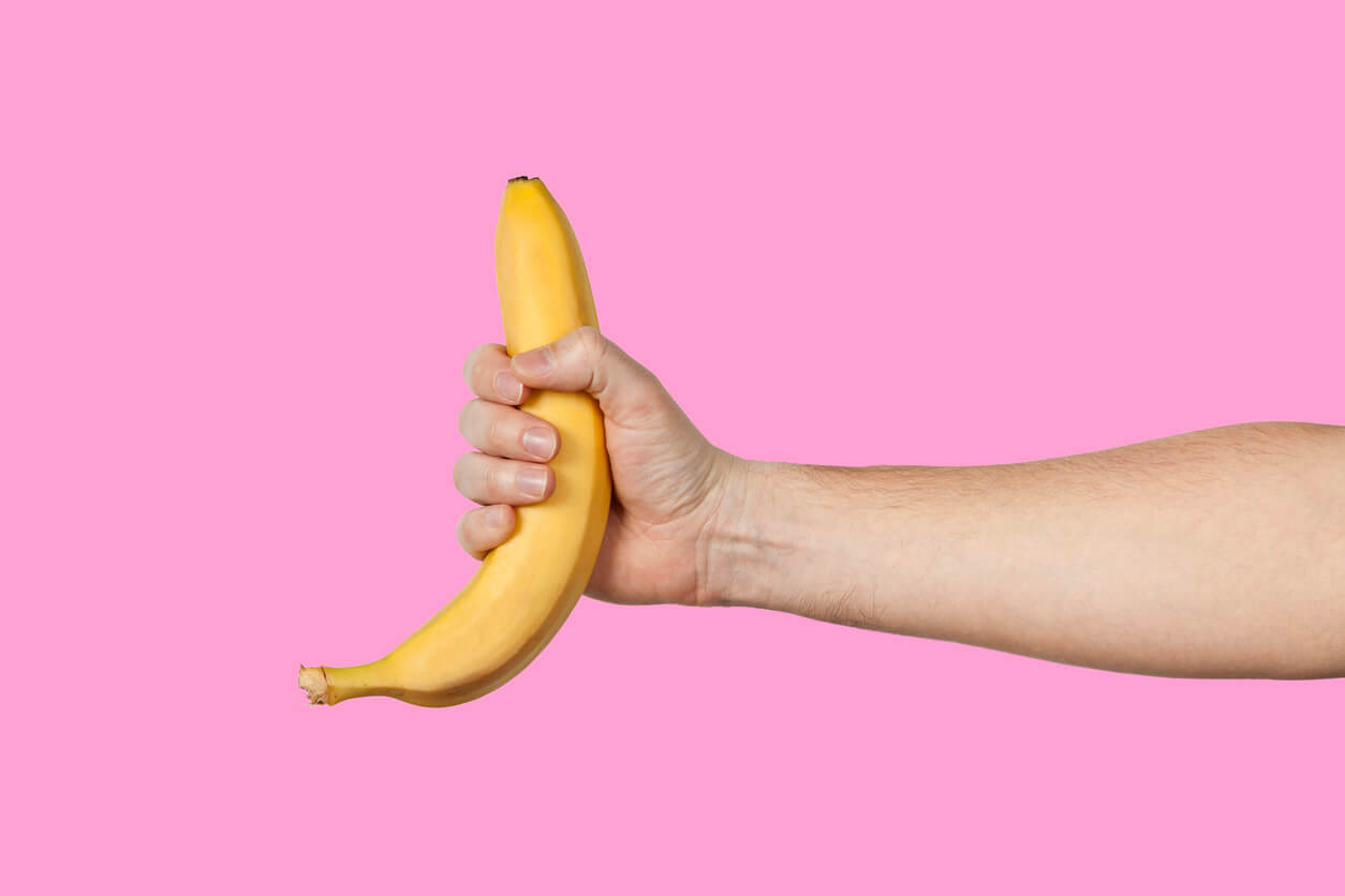 Banana as a Symbol of Male Penis in Hand on a Yellow Background Hidden by Censorship